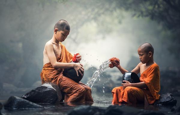 川で鉢を洗っているタイの僧